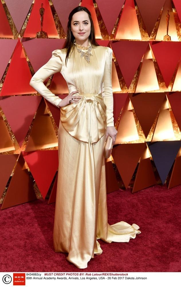 Dakota Johnson w złotej sukni pozuje na czerwonym dywanie podczas Oscarów 2017