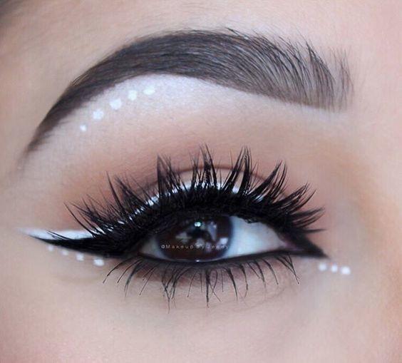 Makijaż oka z bliska z czarną jaskółką i białymi kropkami