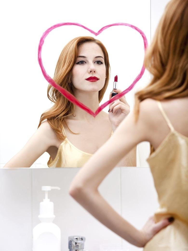 kobieta przed lustrem z namalowanym sercem