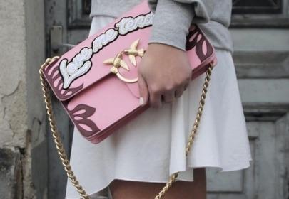 różowa torebka z napisem na łańcuszku dziewczyna trzyma torebkę