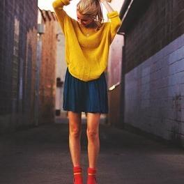 Dziewczyna w żółtym swetrze, granatowej rozkloszowanej spódniczce, czerwonych skarpetkach i żółtych sandałkach na obcasie