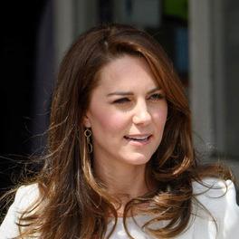 Księżna Kate w białej marynarce uśmiecha się szeroko