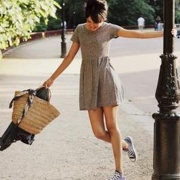Dziewczyna w szarej sukience i granatowych trampkach trzyma się za latarnię uliczną i macha kapeluszem