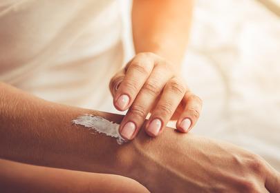 Zbliżenie na rękę oraz dłoń, która smaruje skórę białym balsamem
