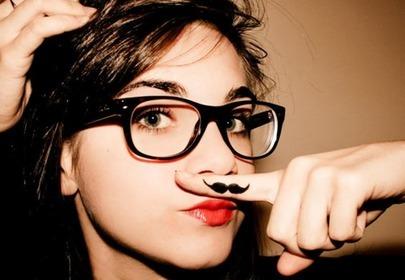 dziewczyna w okularach z namalowanym wąsikiem na palcu