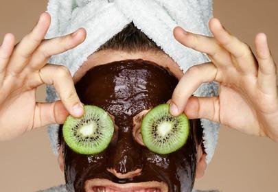 Kobieta z białym ręcznikiem na głowie, w białym szlafroku z twarzą pomalowaną czekoladą i plasterkami zielonego kiwi zamiast oczu