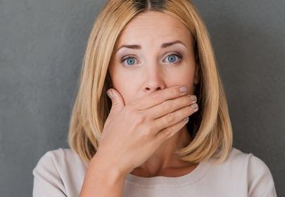 kobieta zasłania dłonią usta