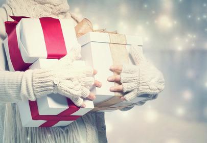 kobieta trzyma w dłoniach wiele prezentów
