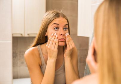 kobieta sprawdza cienie pod oczami