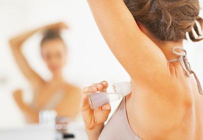 Dziewczyna w białej pokoszulce stoi przed lustrem z ręką uniesioną do góry i smaruje pachy natyperpspirantem