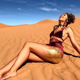 kobieta z pośladkami pokrytymi brokatem leży na plaży w bikini
