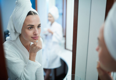 kobieta wciera krem w twarz patrząc w lusterko