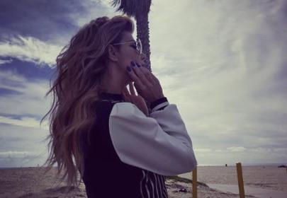 edyta górniak z rozwianymi włosami chodzi po plaży o zachodzie słońca w Los Angeles