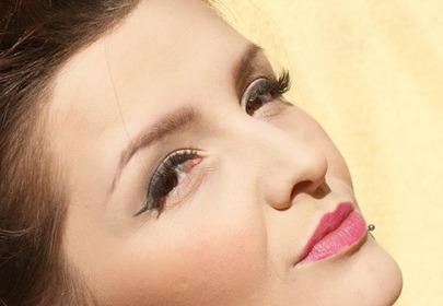 Dziewczyna w makeup-ie patrzy się z przymrużonymi oczami